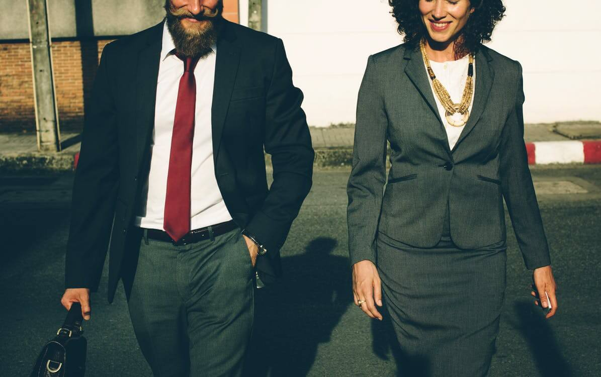 Man and woman in business attire walking next to each other