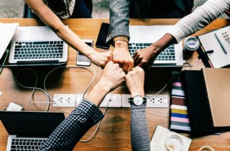 A bunch of employees sharing a fist bump over a conference table at a meeting.