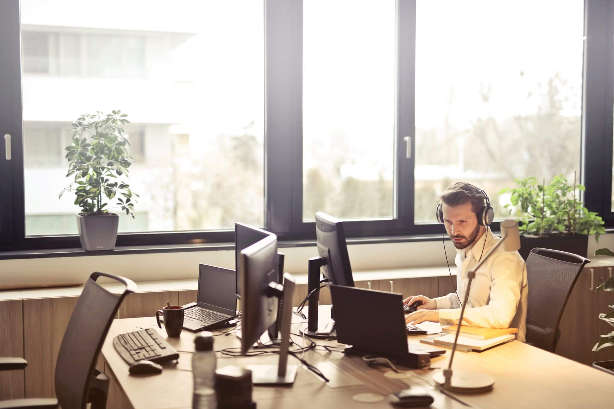 Solo business guy with a headset sitting at a desk typing on the computer.