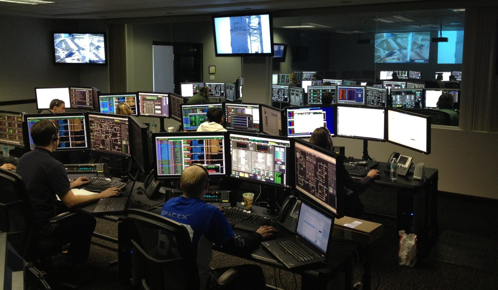 Dark room of computer screens. Looks like a hub for security or IT.
