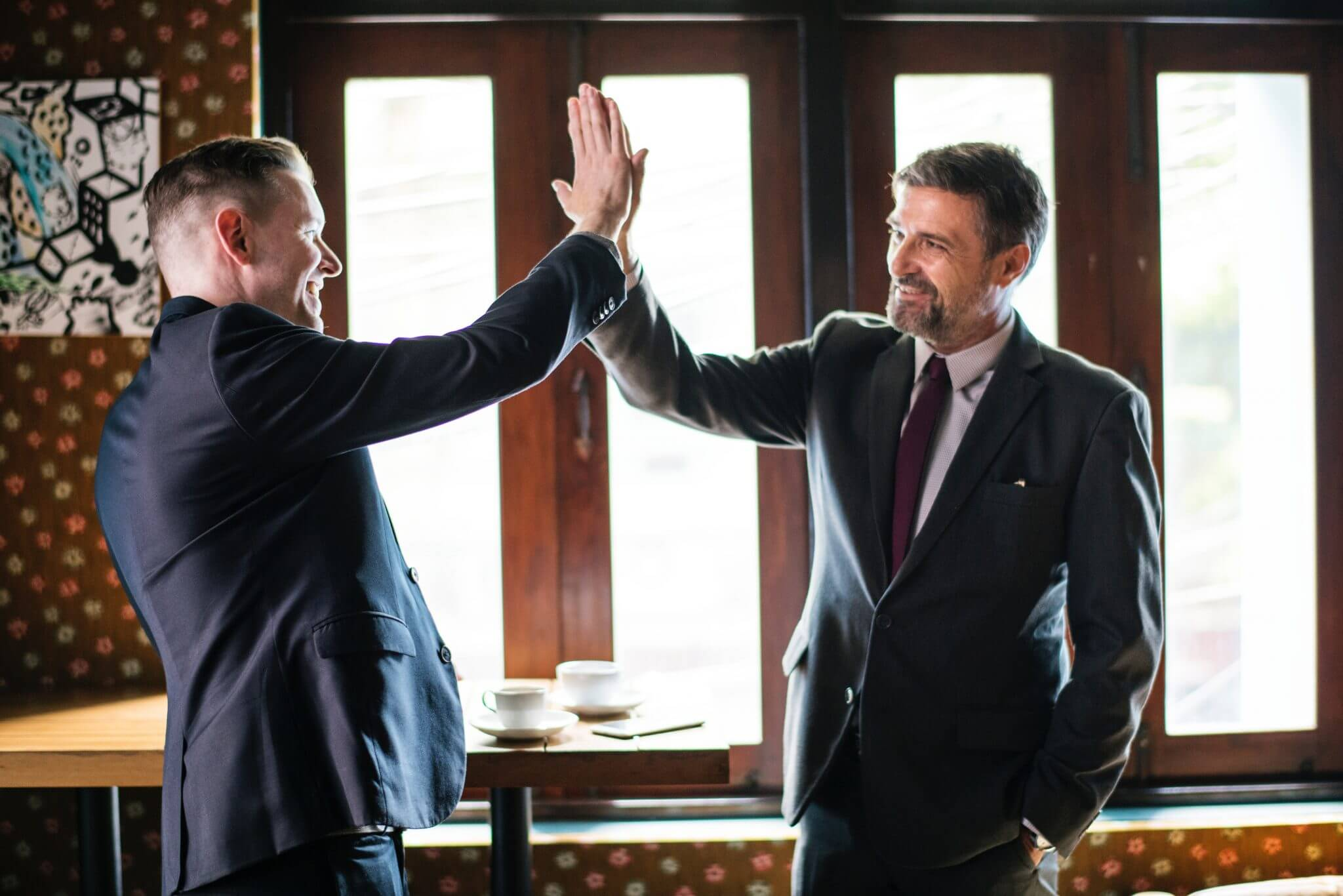 Two men in business suit attire high-fiving each other and smiling.