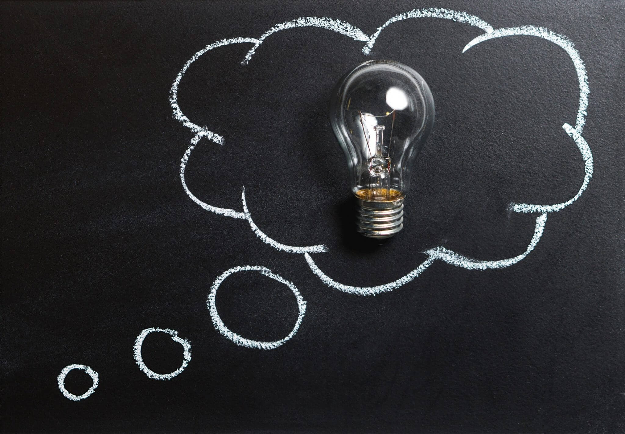 light bulb within a thought bubble on a chalkboard signifying an idea or something clever.