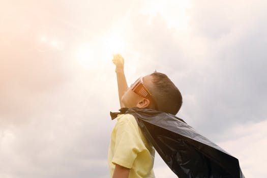 Little kid with a hero cape fist bumping the sky