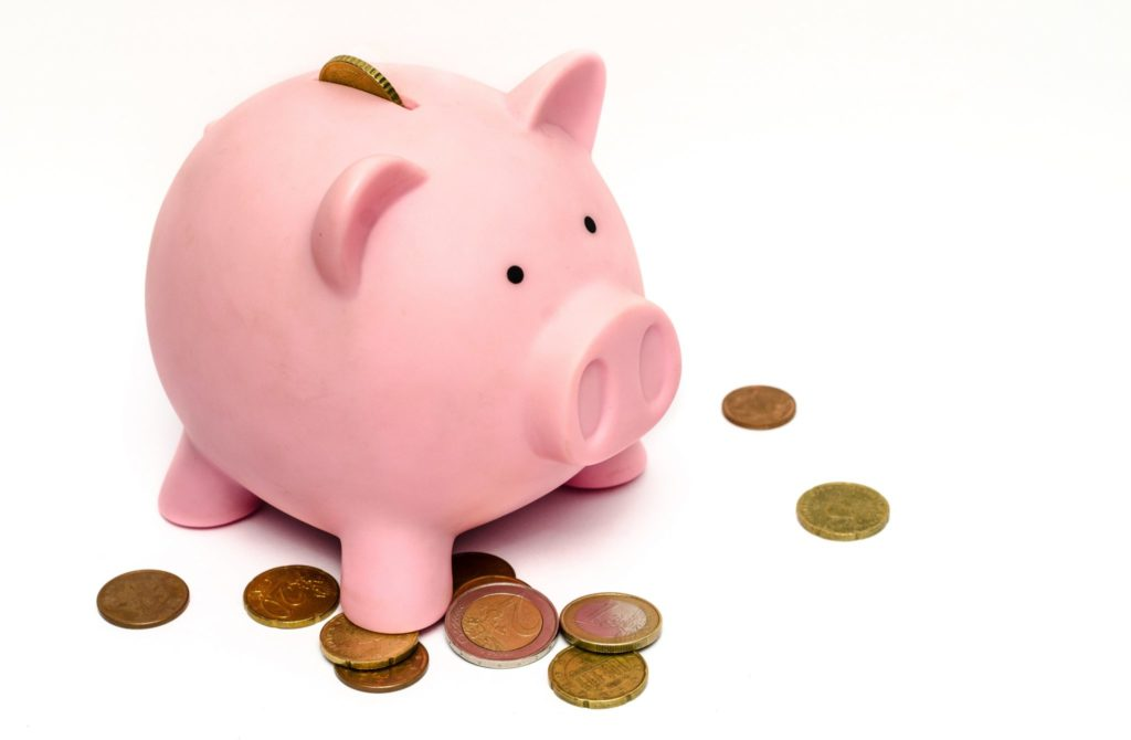 Pink piggy bank with coins around it.