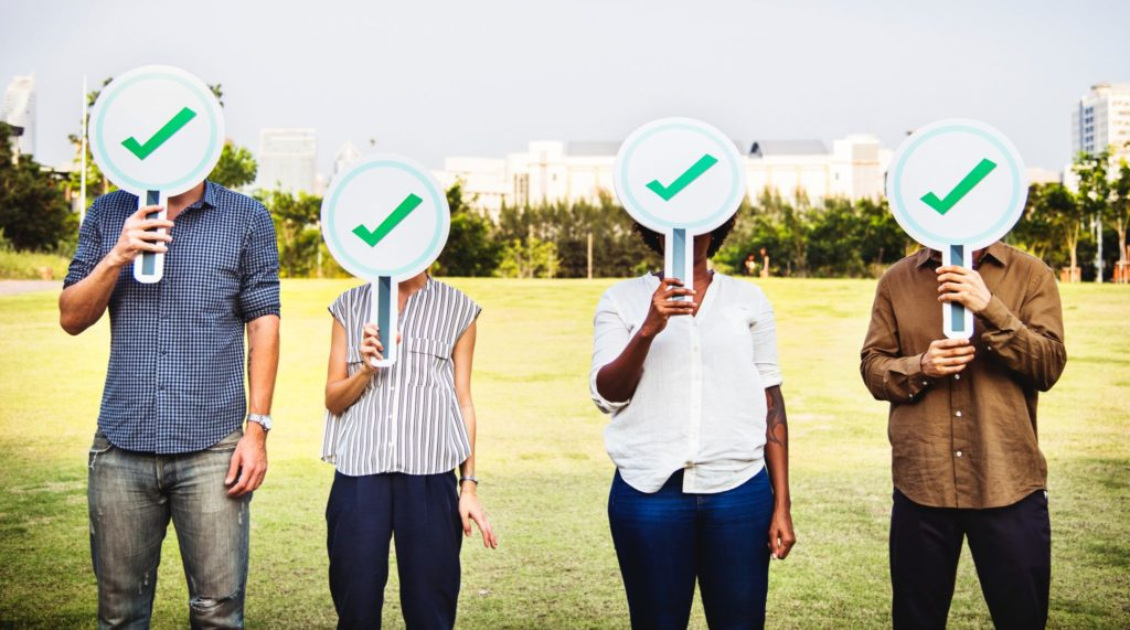 Group of 4 people standing in a field with check mark signs in front of their faces