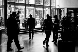 a black and white image of employees walking through a main entranceway.