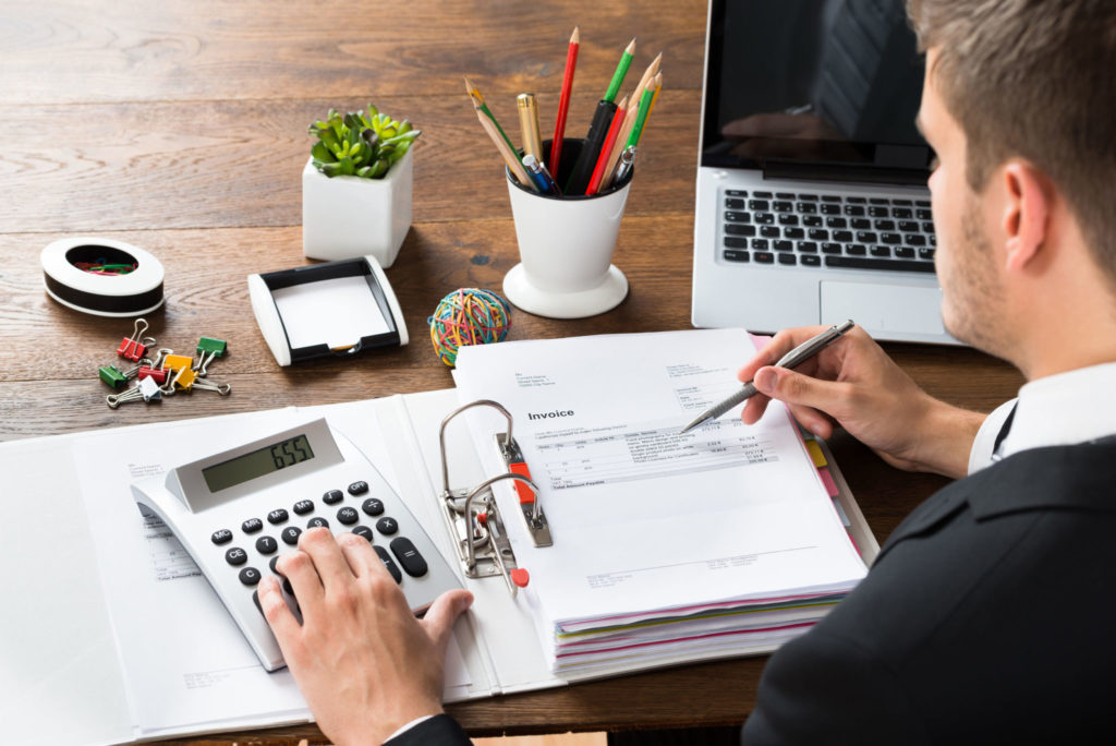 close-up of businessman calculating receipt with calculator at desk