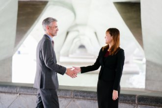 woman shaking hands with a man and smiling