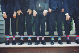 several men in suits standing in a row showing off their colorful socks