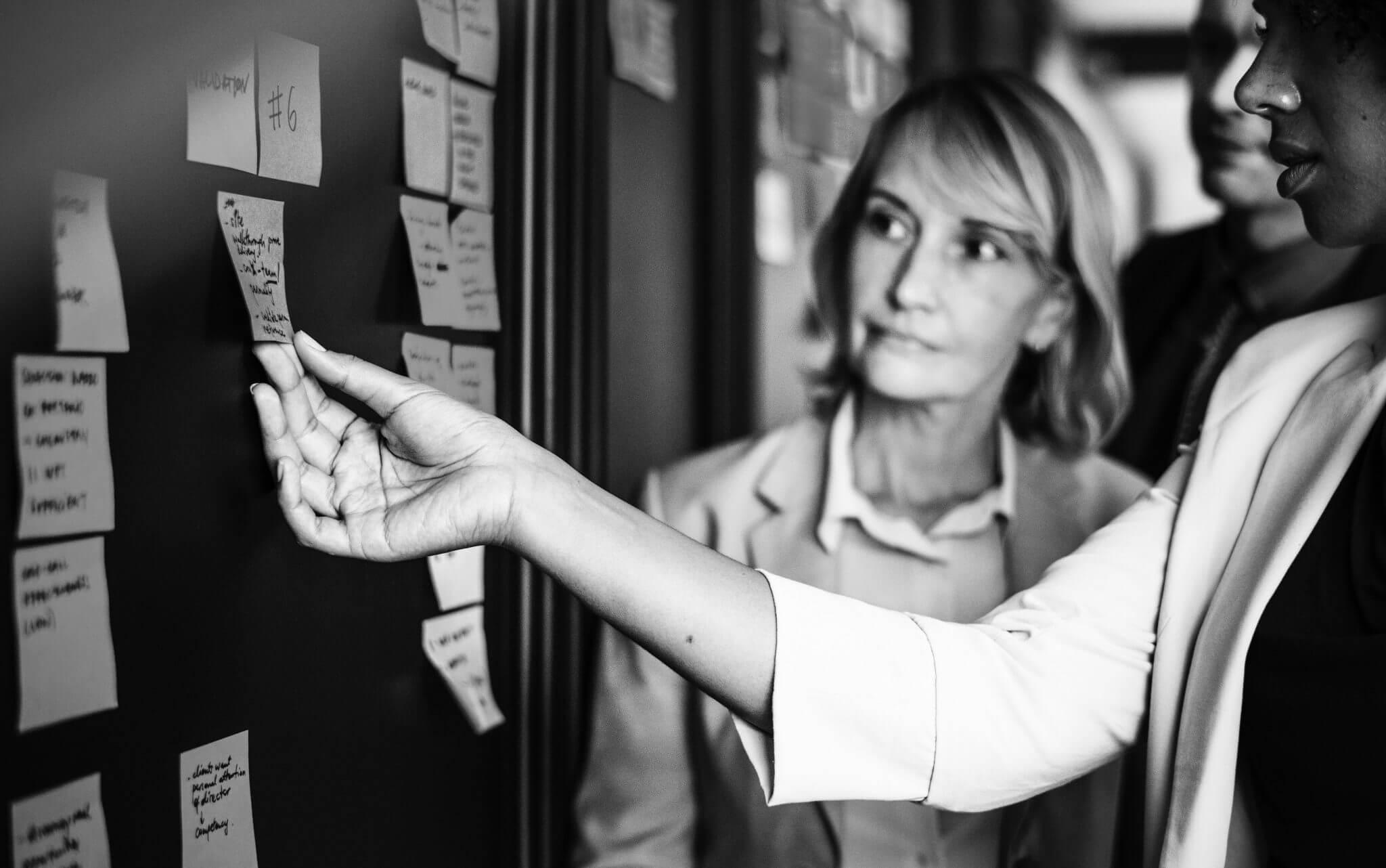 An employee showing her boss an idea on a whiteboard.