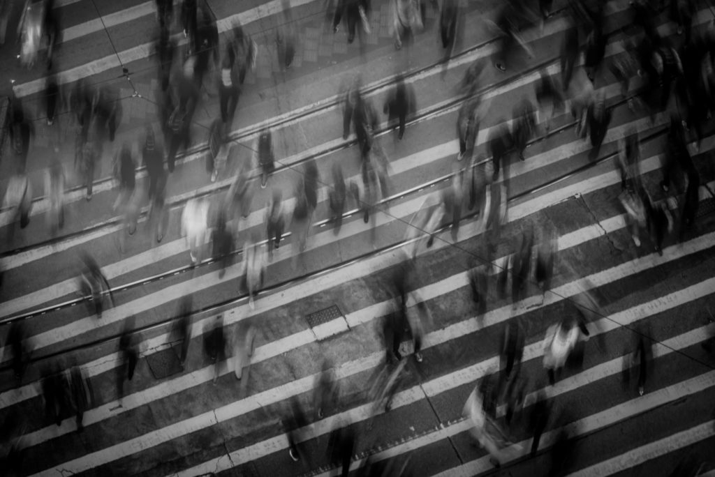 black and white photo of people crossing the street
