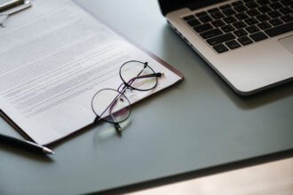 business document on clipboard next to a laptop and reading glasses.
