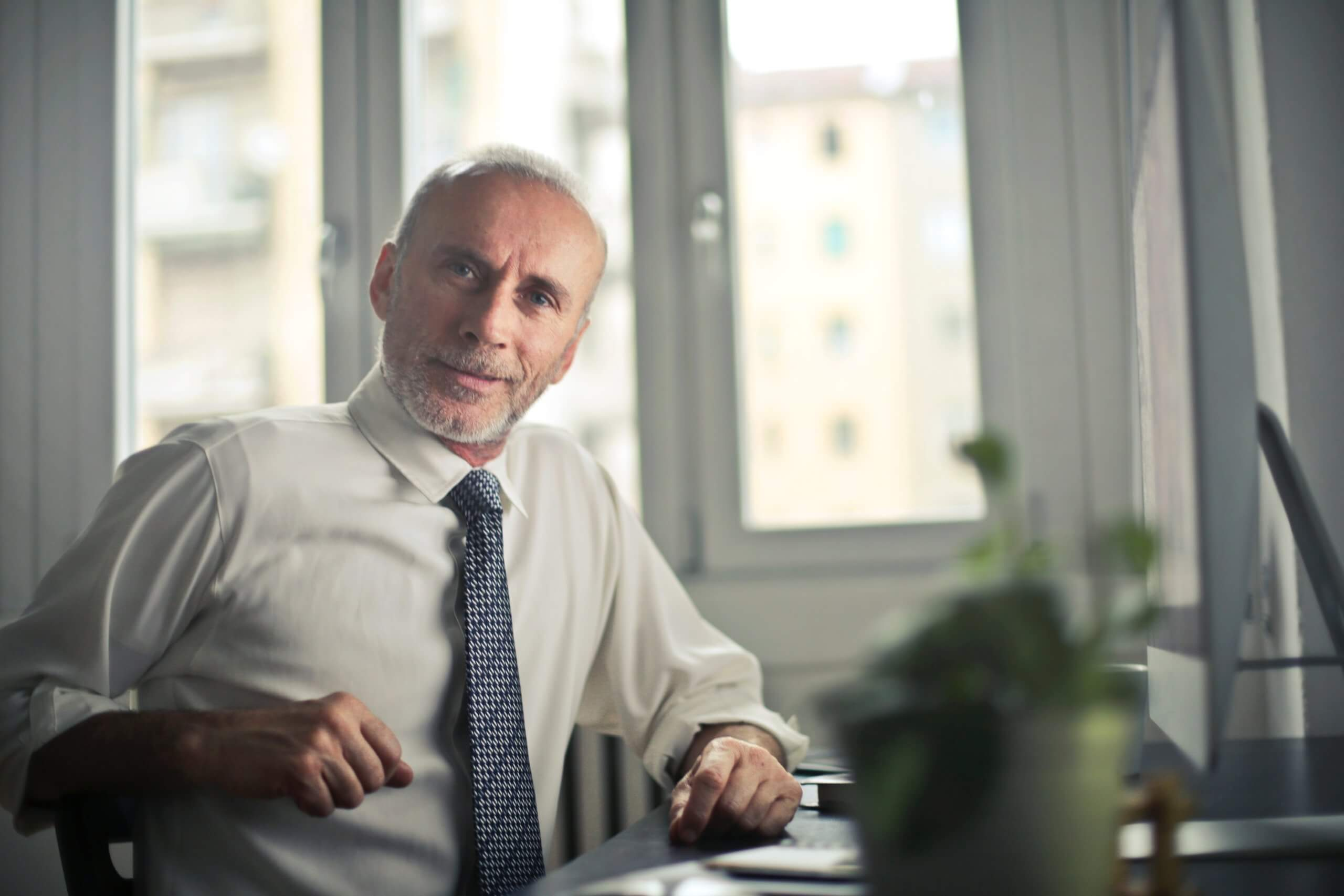 older gentleman in a business shirt and tie sitting at a desk looking at camera