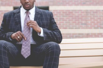 Guy in a business suit adjusting his tie and sitting down.