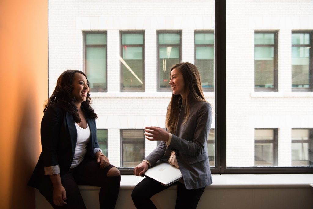 Two women sitting in front of a window talking.
