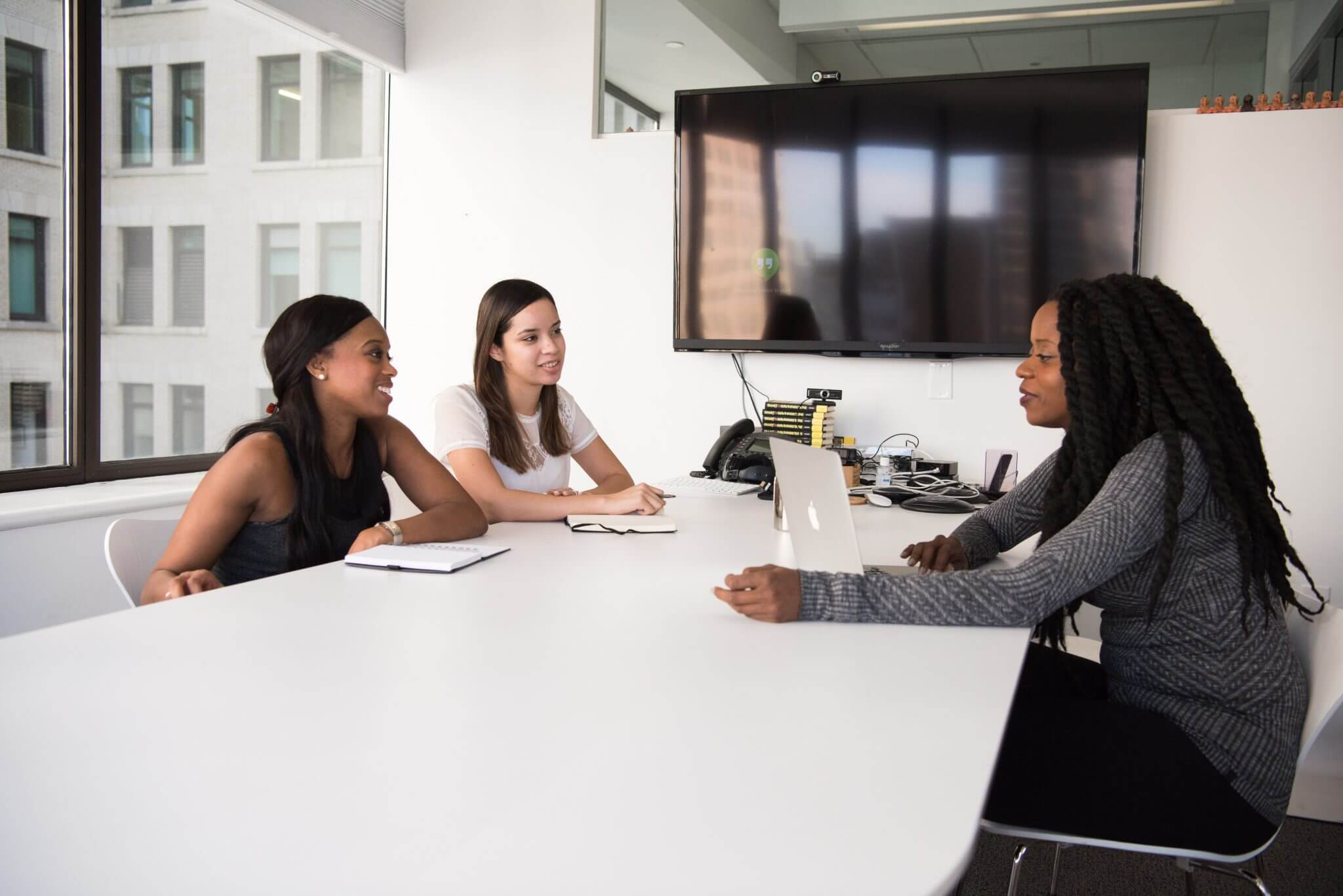 Business women sitting at a conference table having a discussion.