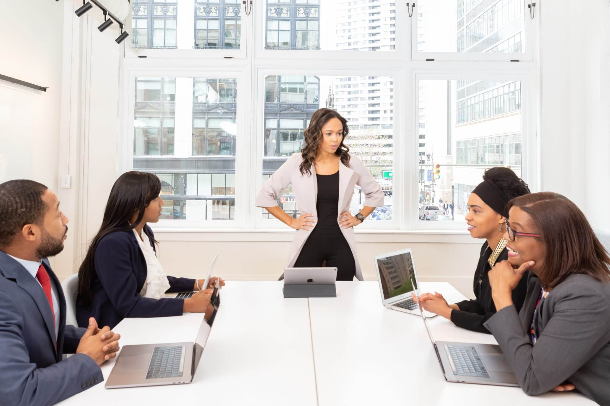 Leader of a company standing in front of a conference table with seated employees