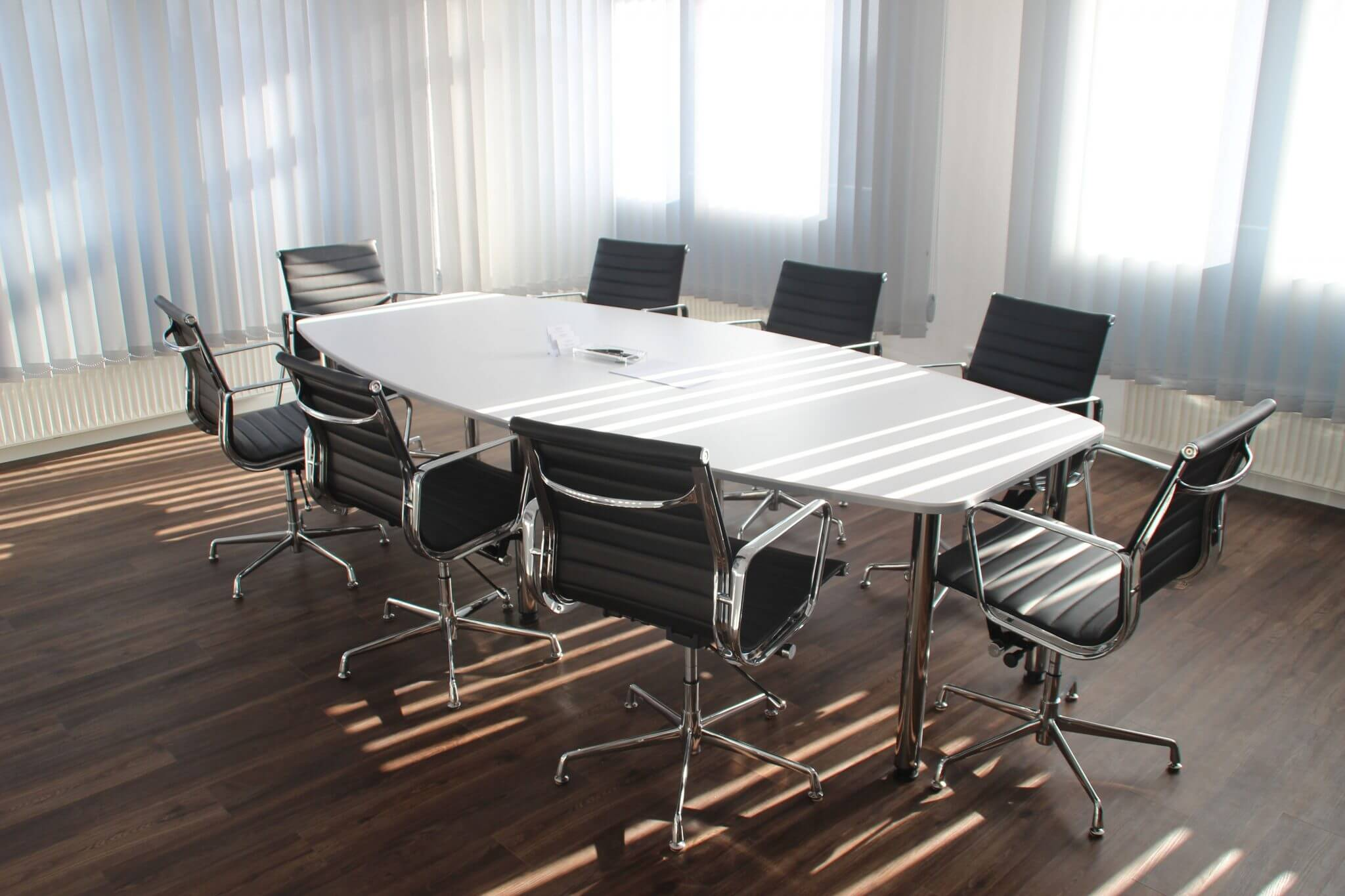 Empty office chairs around an empty conference table.