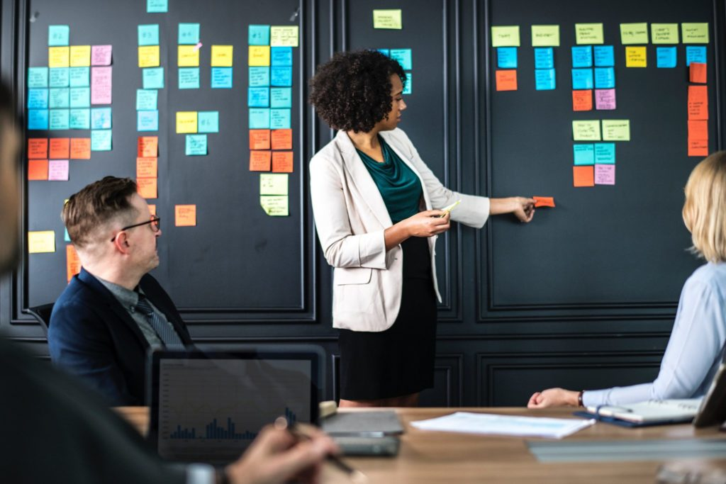 Employee in front of a team, sharing ideas and presenting on sticky notes