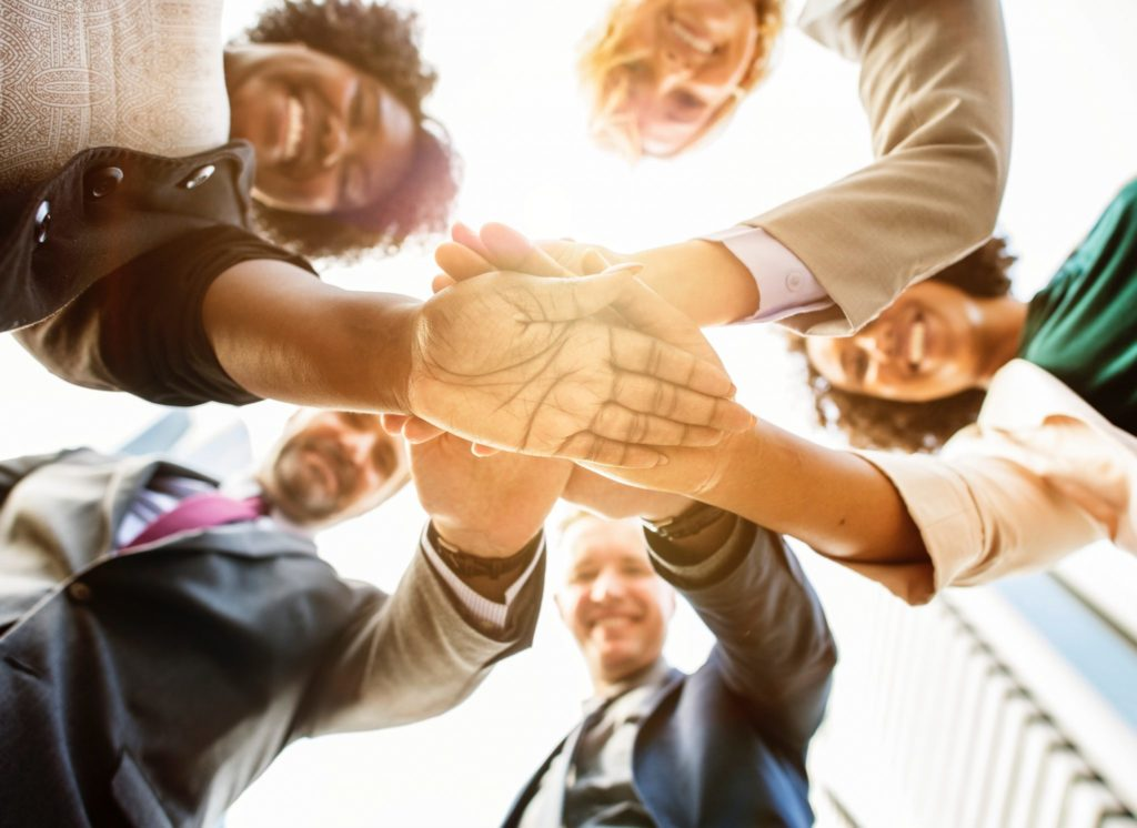 Group of people in a huddle with their hands together