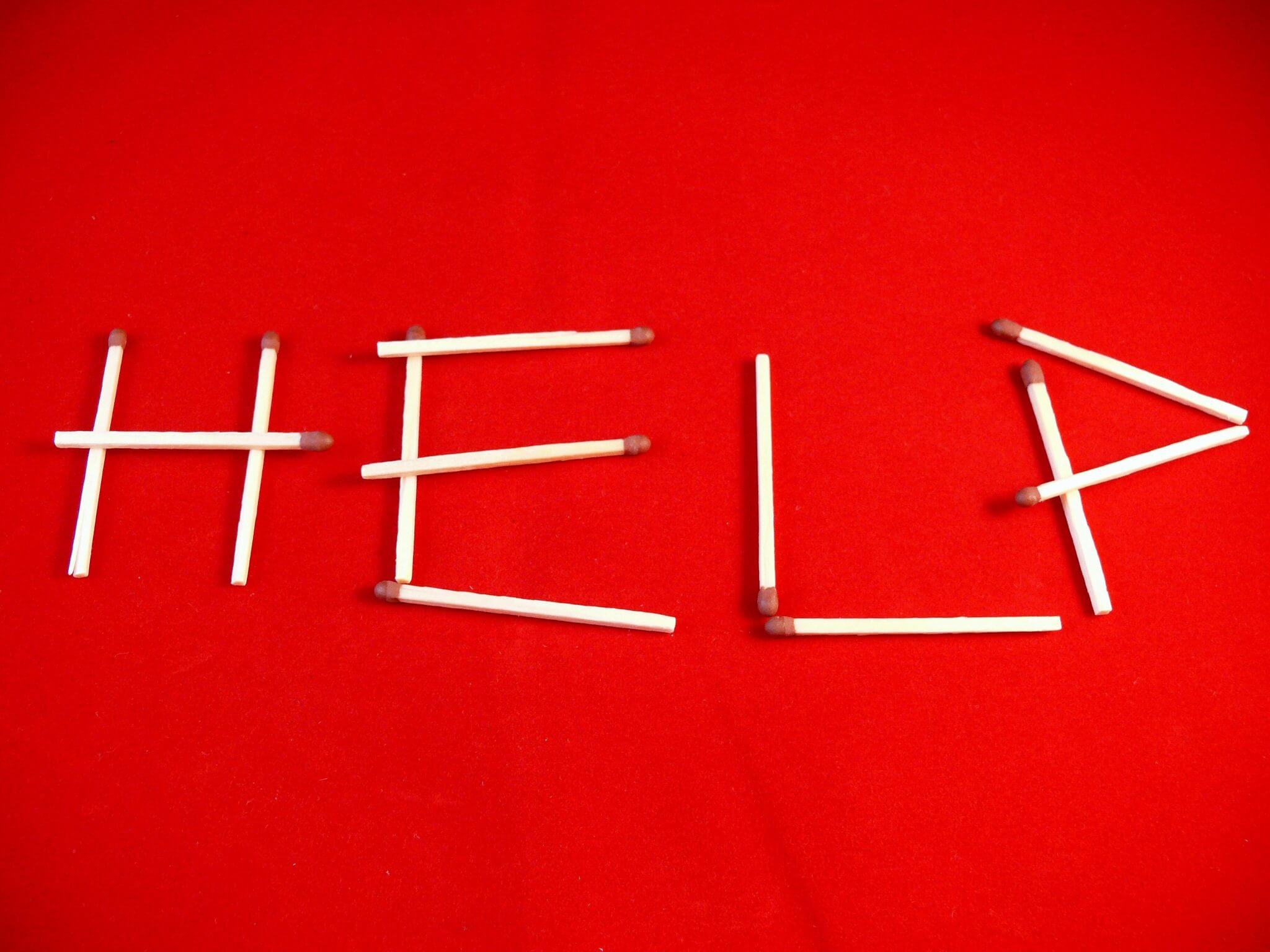 """Red image with the word """"help"""" spelled out in matchsticks."""