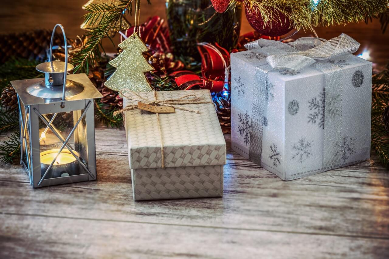 Close up shot of Christmas gifts sitting on the floor near a tree
