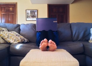 Person sitting on couch with laptop on their lap