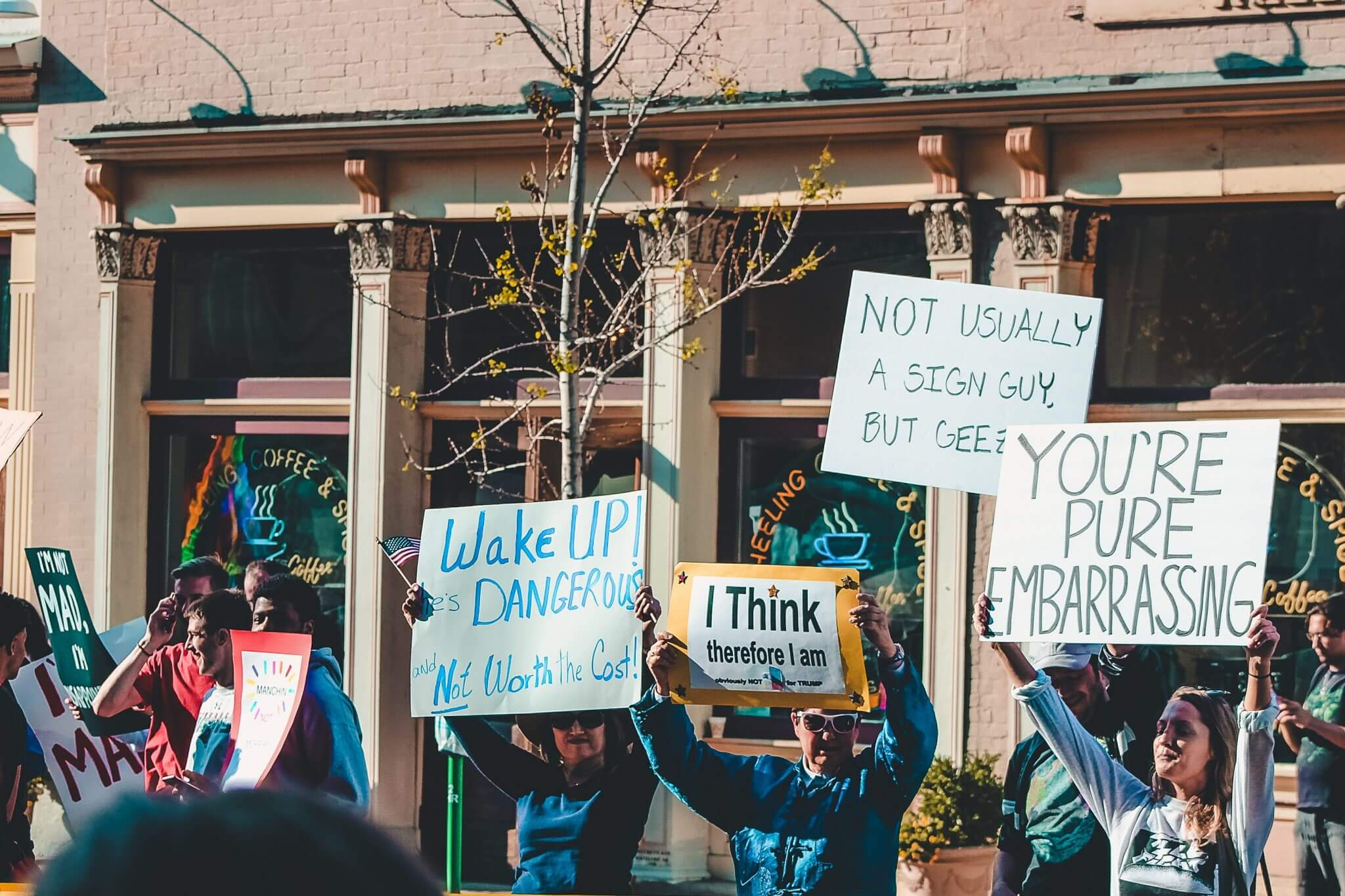 Picture of a rally of protesters holding up signs and demonstrating.