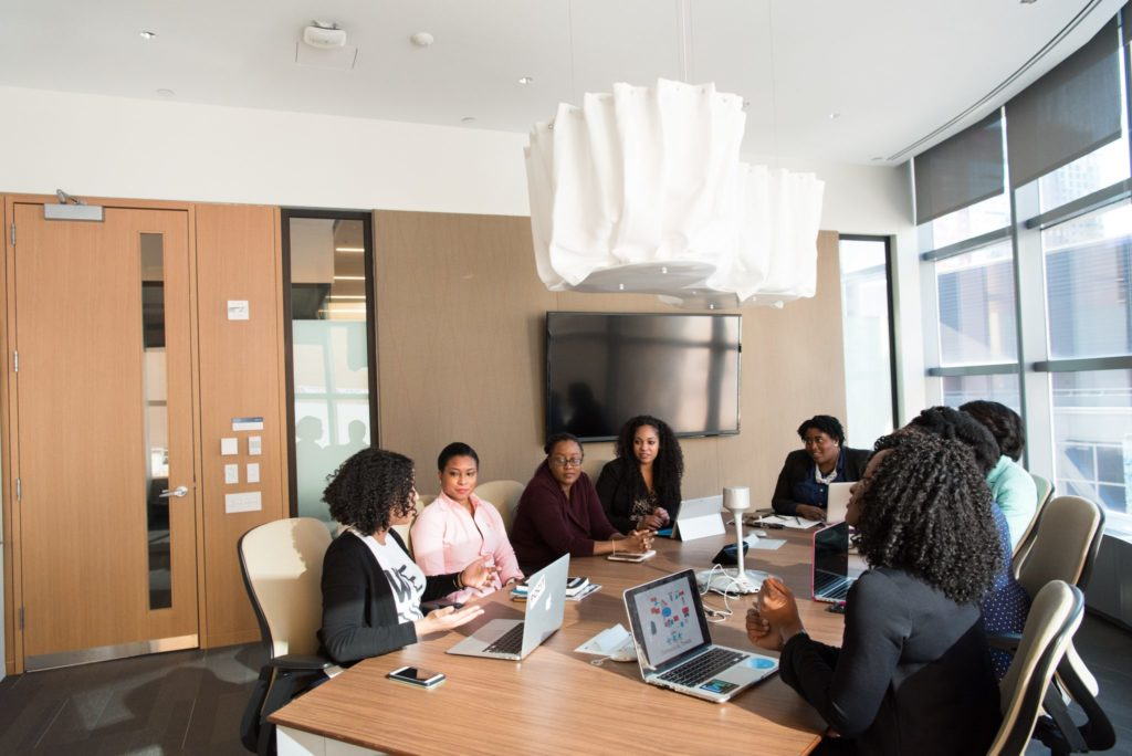 Group of employees sitting around a desk in a conference room having a discussion.