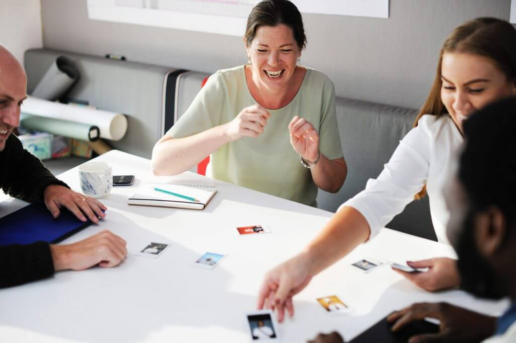 Several employees of a company sitting around a table discussing ideas and talking lightheartedly.