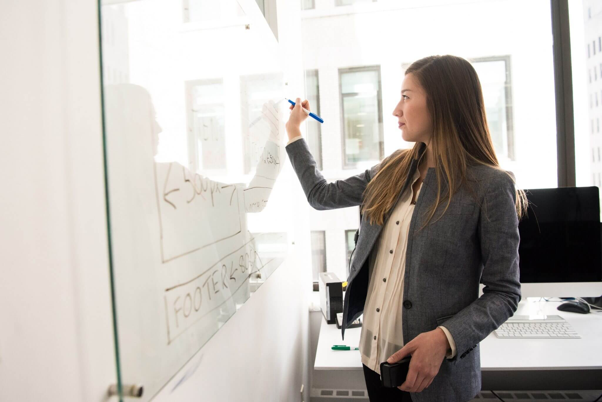Woman standing at a white board writing