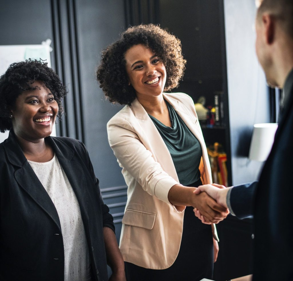 Woman shaking hands with a prospective employer during a first meeting interview.