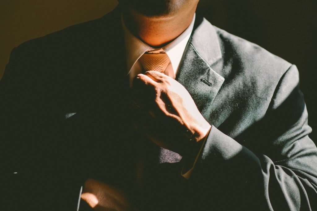 Man in a suit straightening his tie