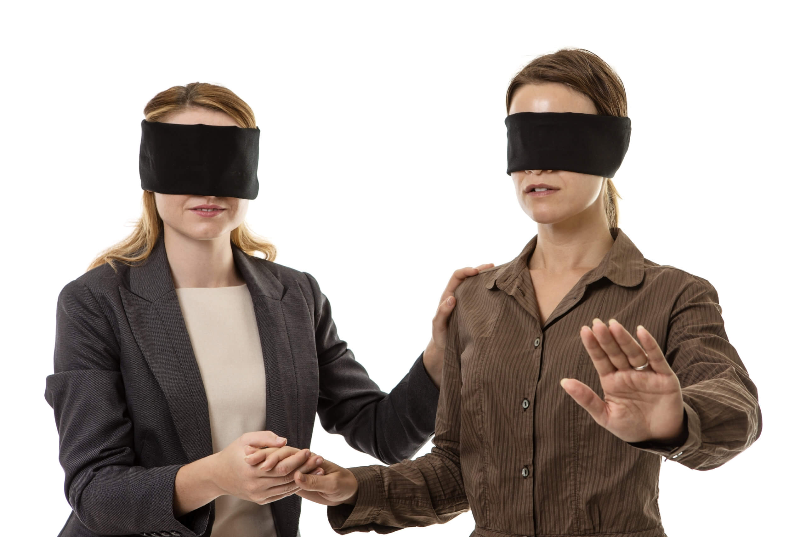 two business woman one blindfolded and the other helping