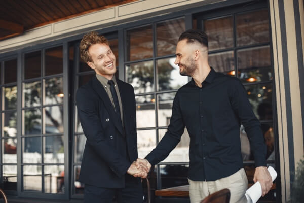 Two men shaking hands during the onboarding process.